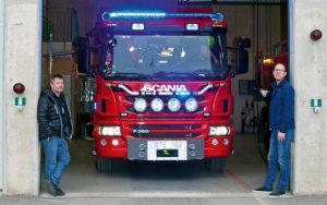 Thomas Isaksson, TMP Alarm och Christer de Wahl, Elektroskandia står framför brandbil på Nynäshamns brandstation.