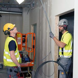 Fredrik Kofoed och Henrik Vintong drar kabel för brandlarmet.